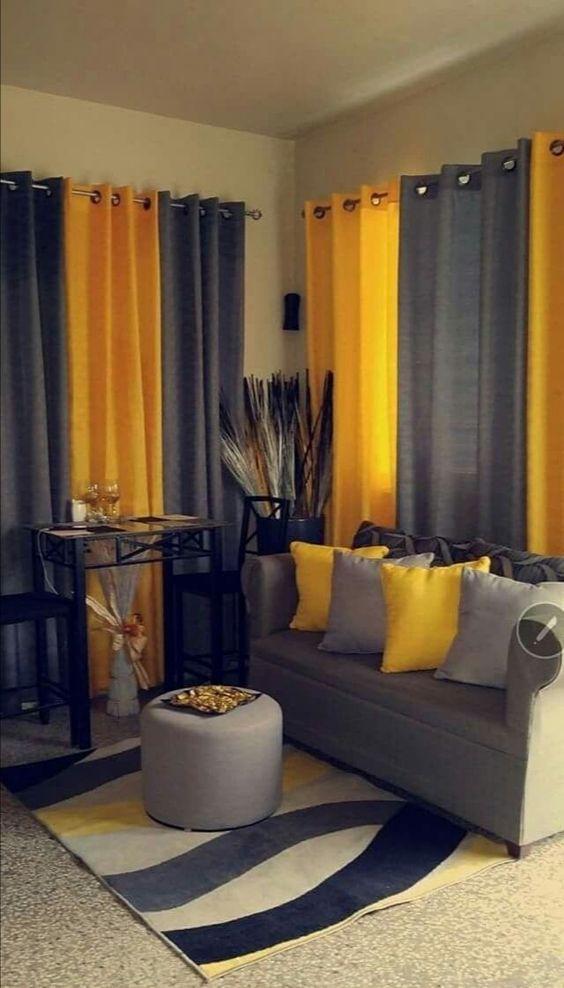 Salón con sofá gris con cojines amarillos y cortina amarilla