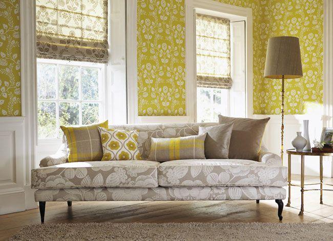 Sofá gris con cojines amarillos estampados