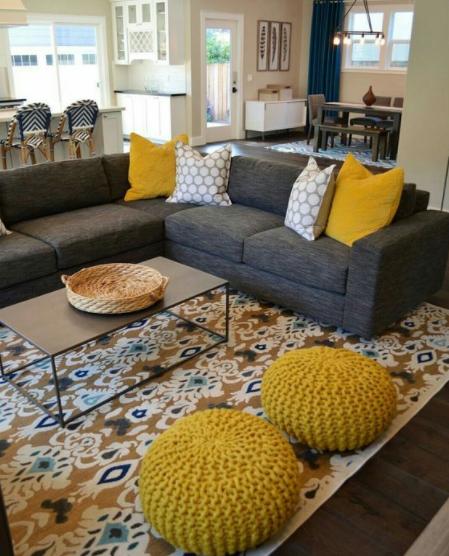 Puffs y cojines amarillos con un sofá gris