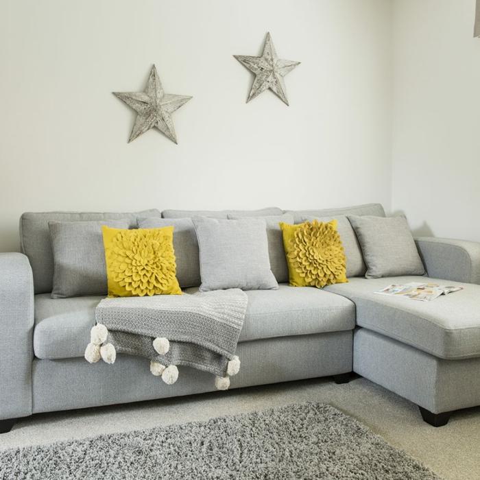 Sofá gris con cojines amarillos floreados en el salón