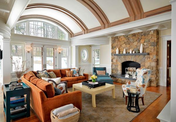 Salón con sofá naranja y con una chimenea de piedra
