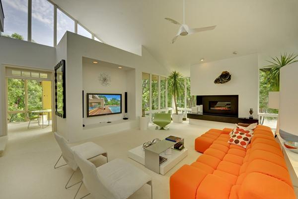 Enorme salón blanco con el toque naranja del sofá