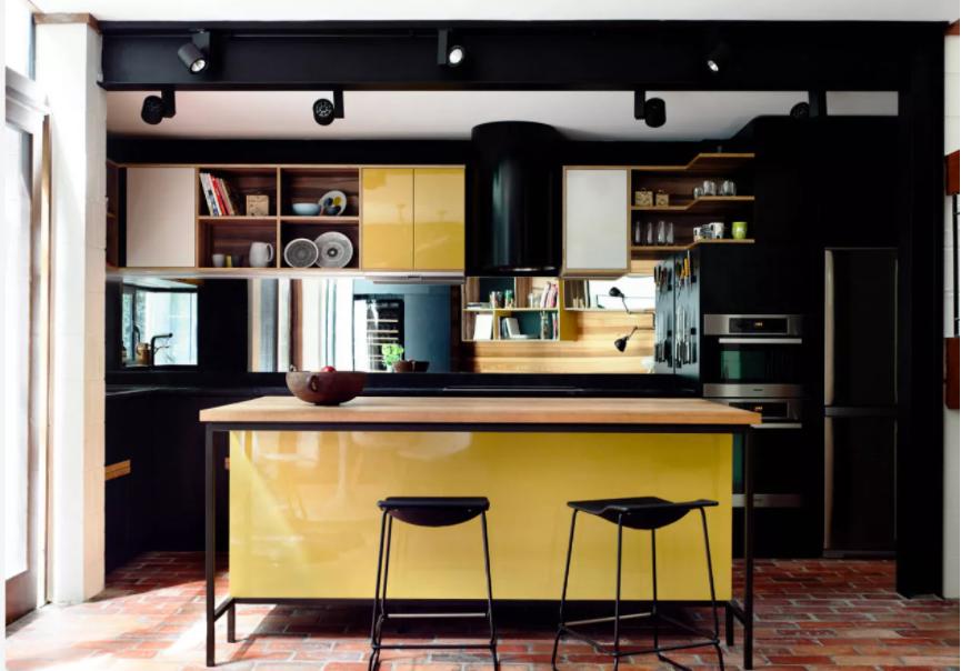 Cocina con paredes negras y muebles amarillos