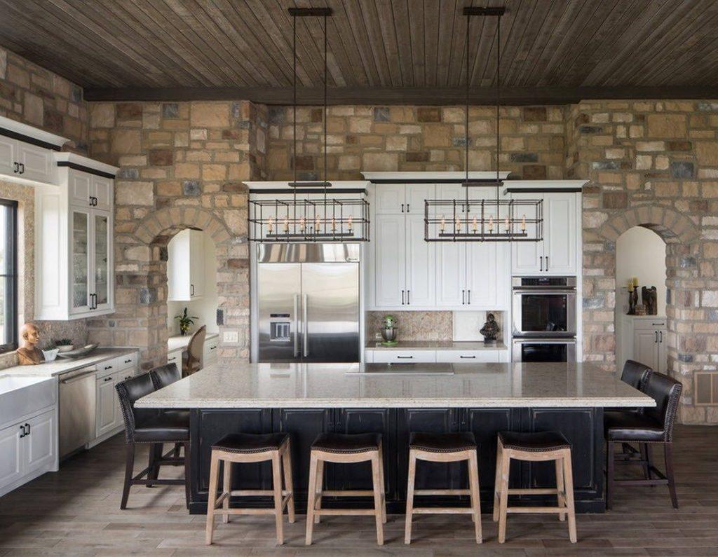 Cocina con piedra y muebles blancos y negros