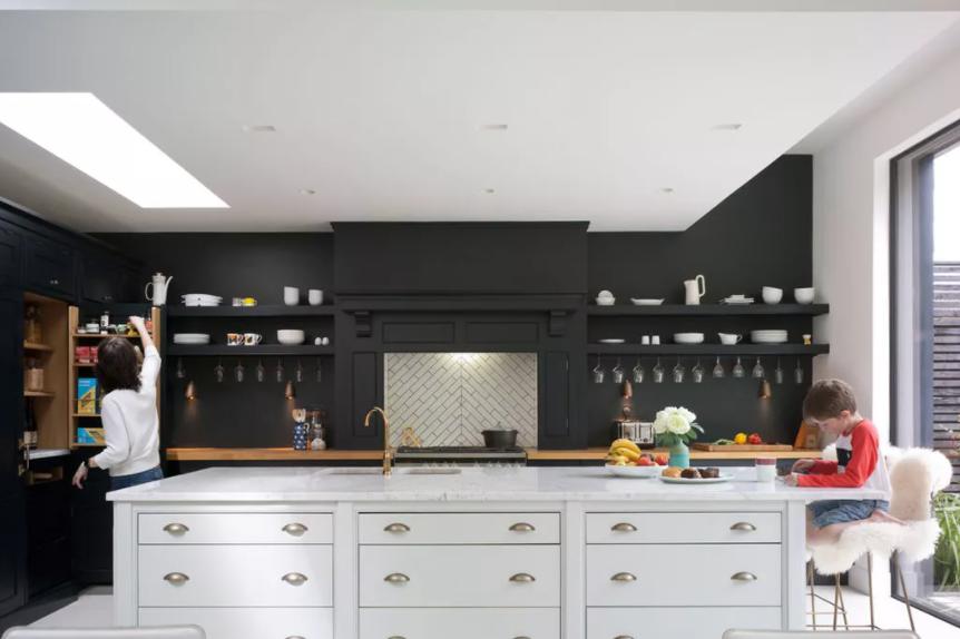 Cocina inglesa con paneles negros en la pared