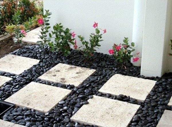 Un suelo elegante con piedras de río negras en un jardín pequeño