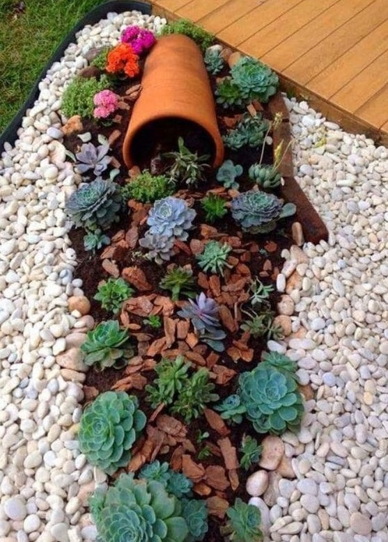 macetas derramadas en un jardin pequeña con flores y piedras