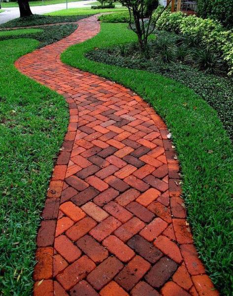 Un pequeño sendero hecho de ladrillos en el jardín