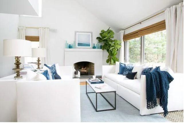 Salón de muebles blancos con cojines azules
