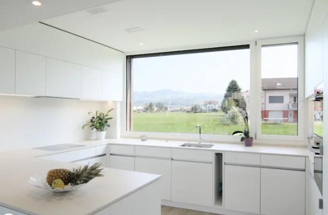 Cocina con gran ventana amueblada en blanco