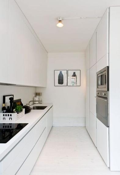 Cocina alargada con muebles en blanco