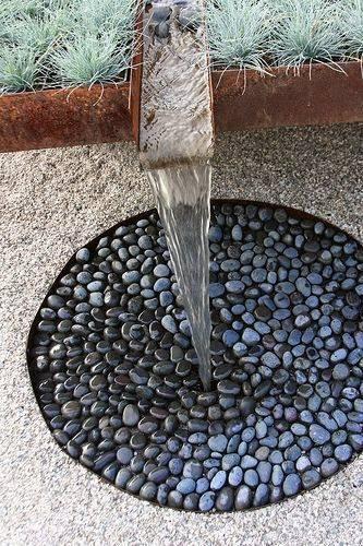 pequeña fuente de agua con piedras de río
