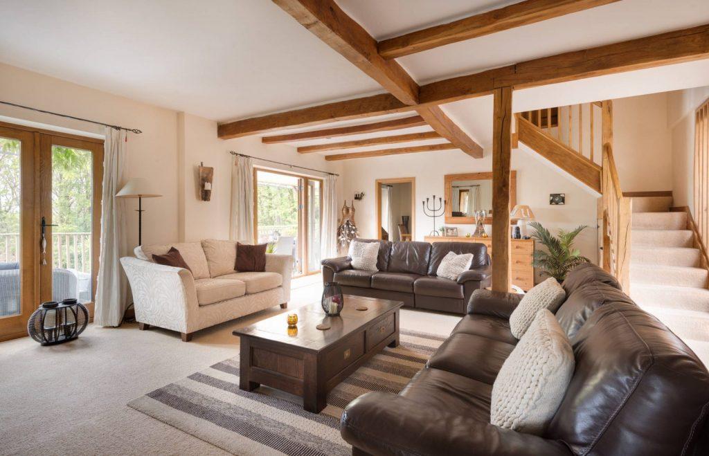 Combina vigas de madera con mobiliario marrón en la sala