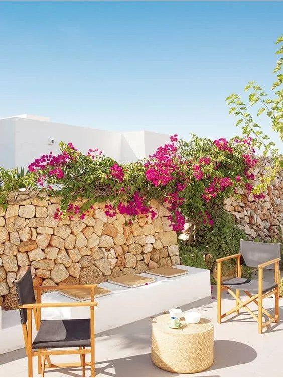Salón al aire libre frente a  una pared exterior de piedras con plantas