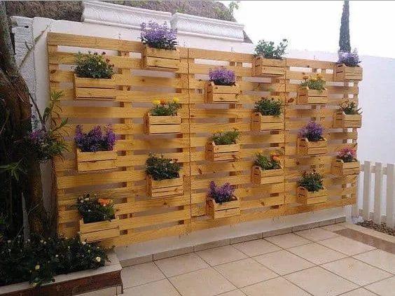 pared exterior de piedras con plantas  en cajas