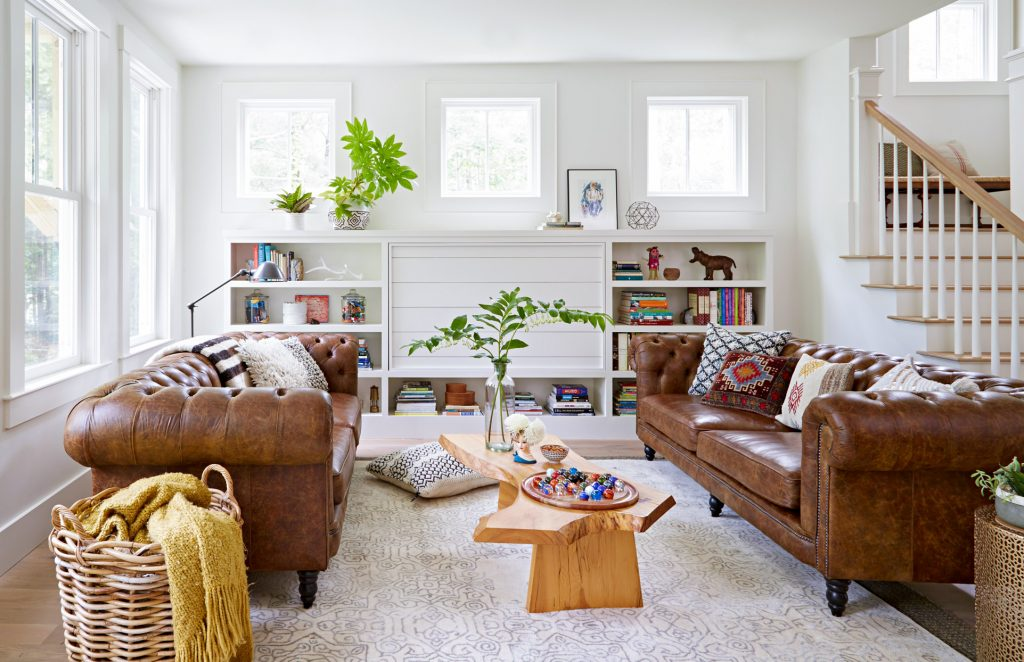 Salón con sofá marrón y paredes blancas