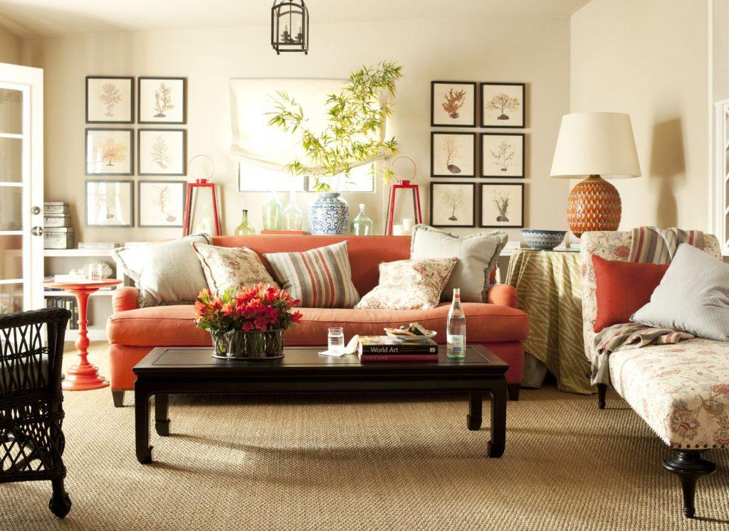 Salón en tonos crema y sofá naranja para dar color