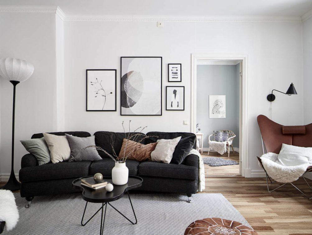 Salón nórdico con sofá oscuro