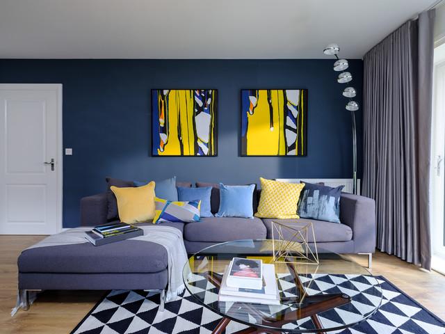 Sofá gris con cojines amarillos y azules