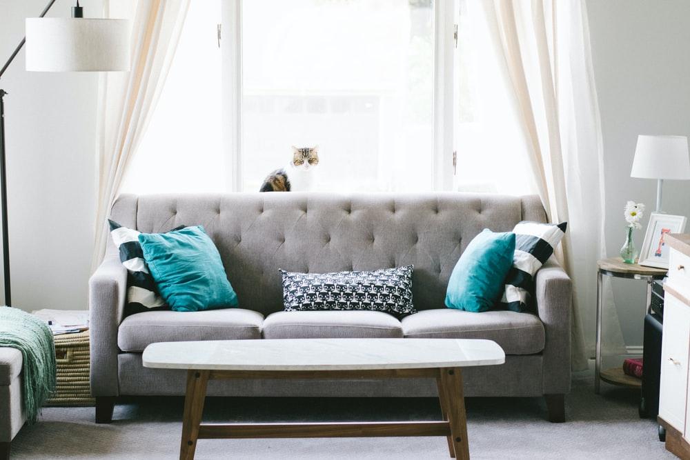 Sofá gris con cojines azules turquesa en el salón