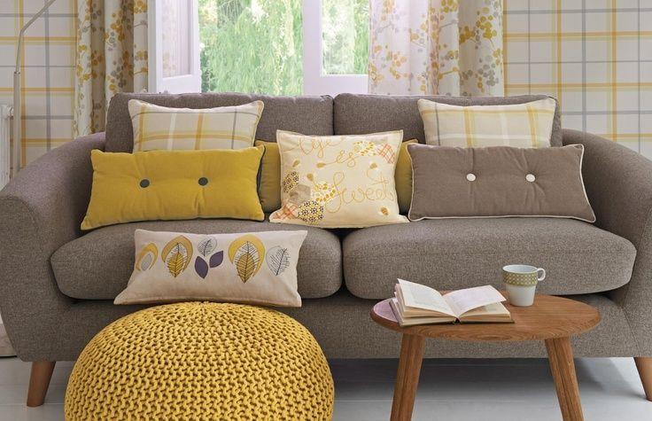 Sofá marrón grisáceo con cojines amarillos