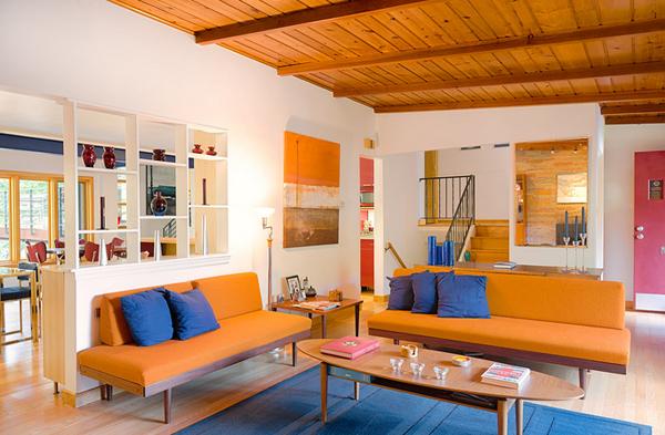 Sofás naranjas con diseño moderno en salón con techo de madera