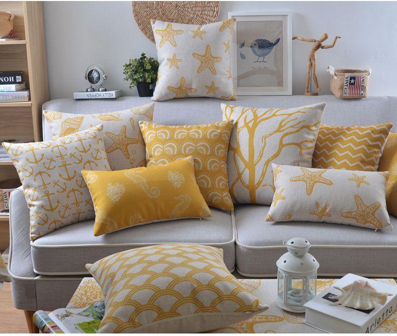 sofá gris con cojines decorativos amarillos