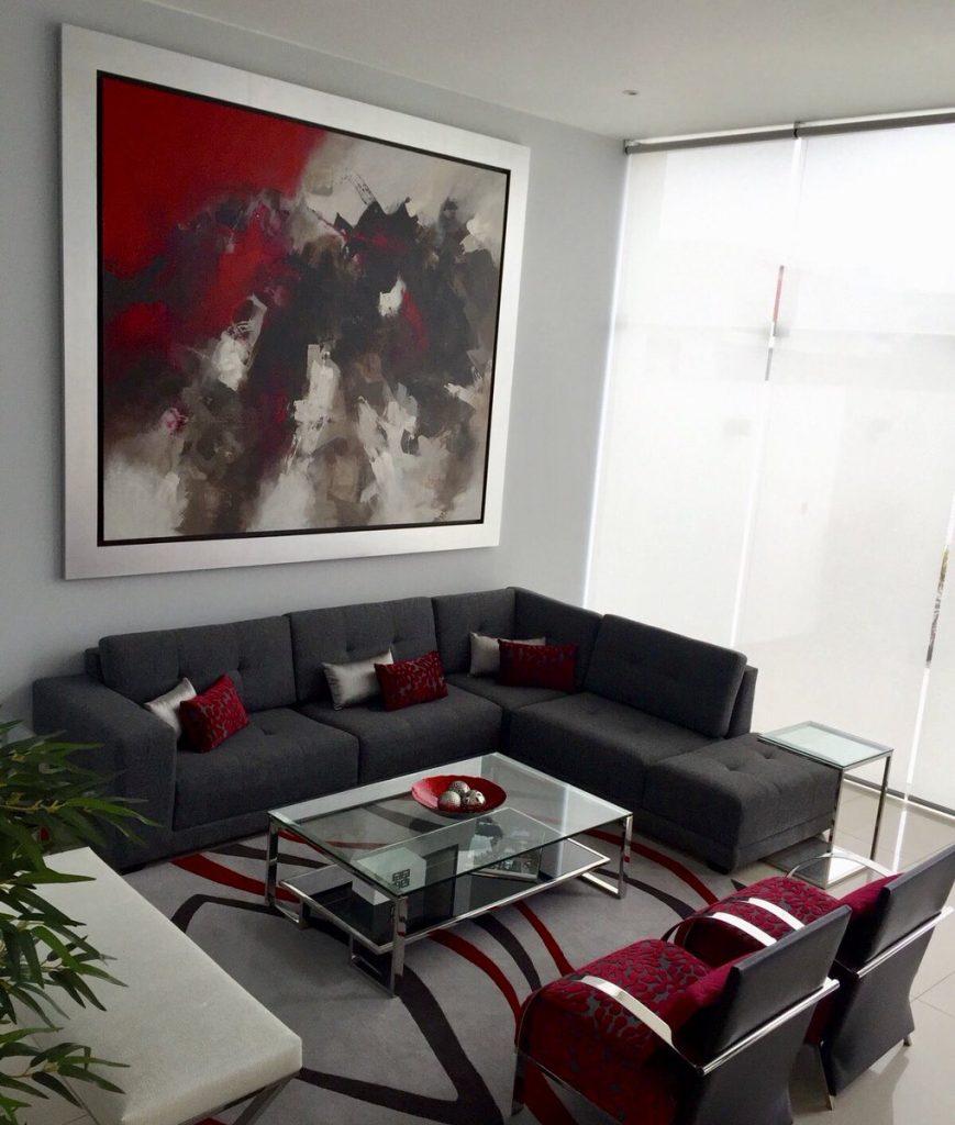 Sofá gris oscuro con cojines rojos y butacas juego