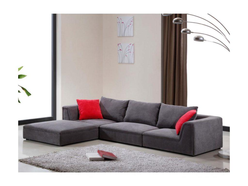 Sofá gris en forma de L y cojines rojos